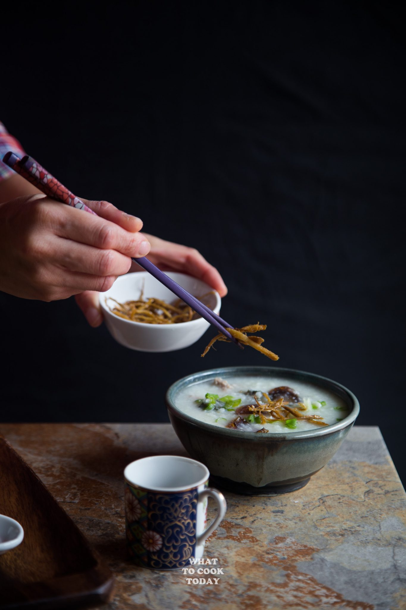 Pork and century egg congee (Bubur pitan) with crispy ginger