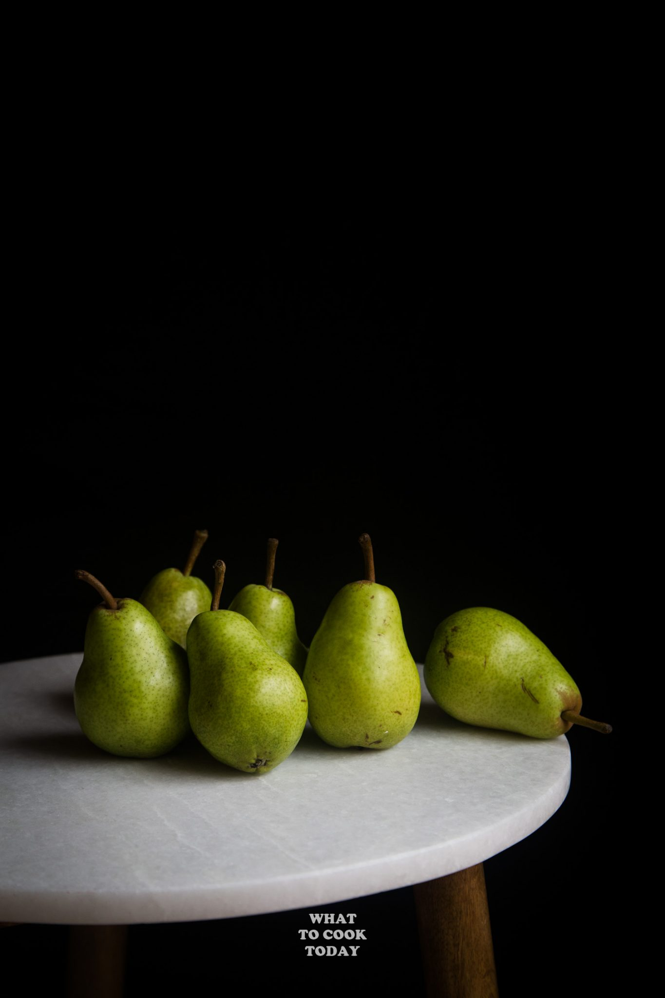 6 bosc pears on marble side table