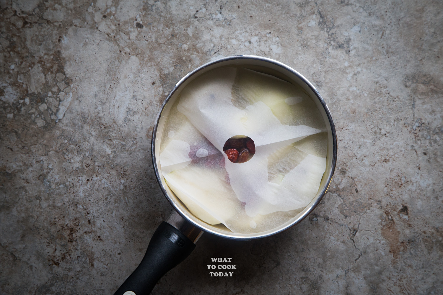longan, red dates, goji berries poached pears covered in parchment paper during poaching