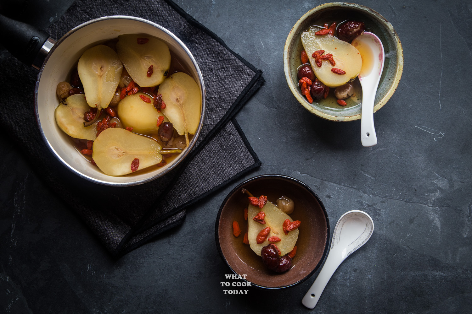 longan, red dates, goji berries poached pears with 2 bowls and spoon in horizontal layout