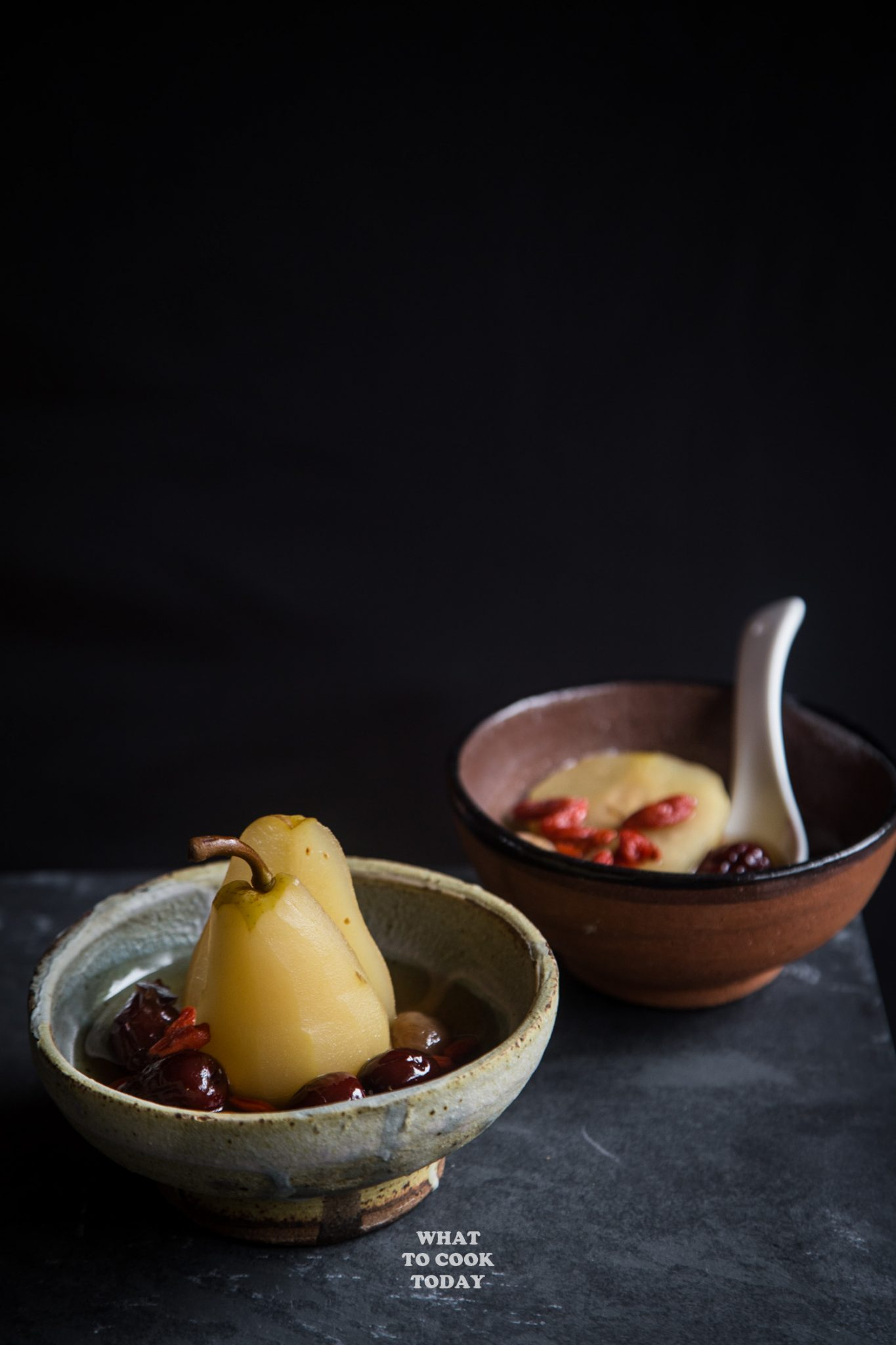 longan, red dates, goji berries poached pears in two bowls ready to be served